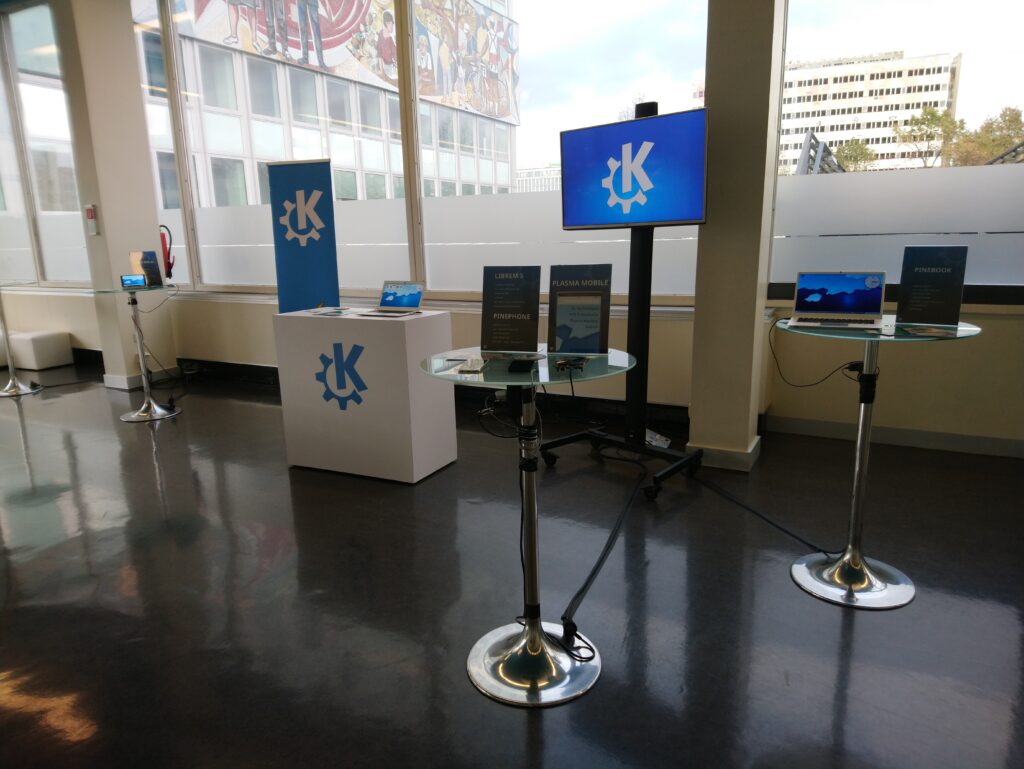 KDE booth at Qt World Summit, shiny black vinyl floor, a KDE-branded table, three bistro tables with devices on them
