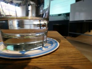 A glass of water sitting on a KDE beer coaster on a wooden table with blurry projector image in the background