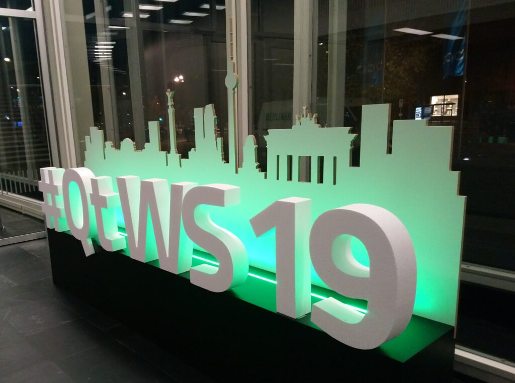 "The letters ""#QtWS19"" 30cm tall of styrofoam with suggested Berlin skyline of cardboard behind"