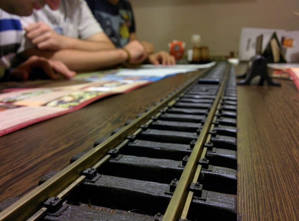 A wooden restaurant table with model railroad tracks on it, where a train would deliver beverages to people sitting at the table